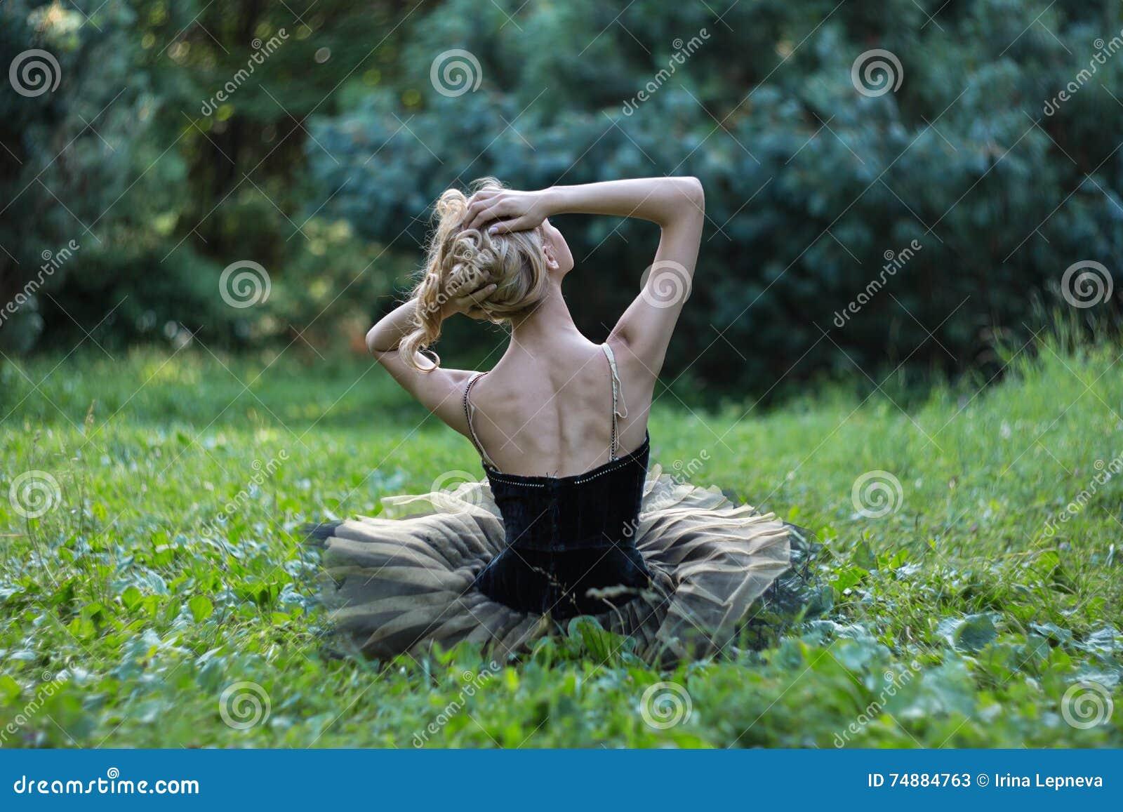 Muchacha hermosa que miente y que descansa sobre una hierba en parque del verano