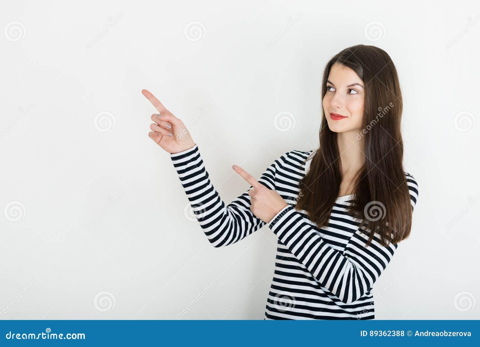 Muchacha hermosa que señala al lado Presentación de su producto Aislado en blanco