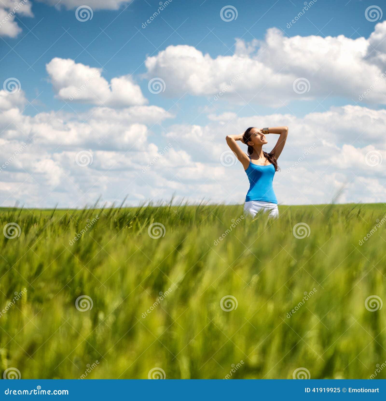 Muchacha hermosa que se relaja en un campo de trigo del verano