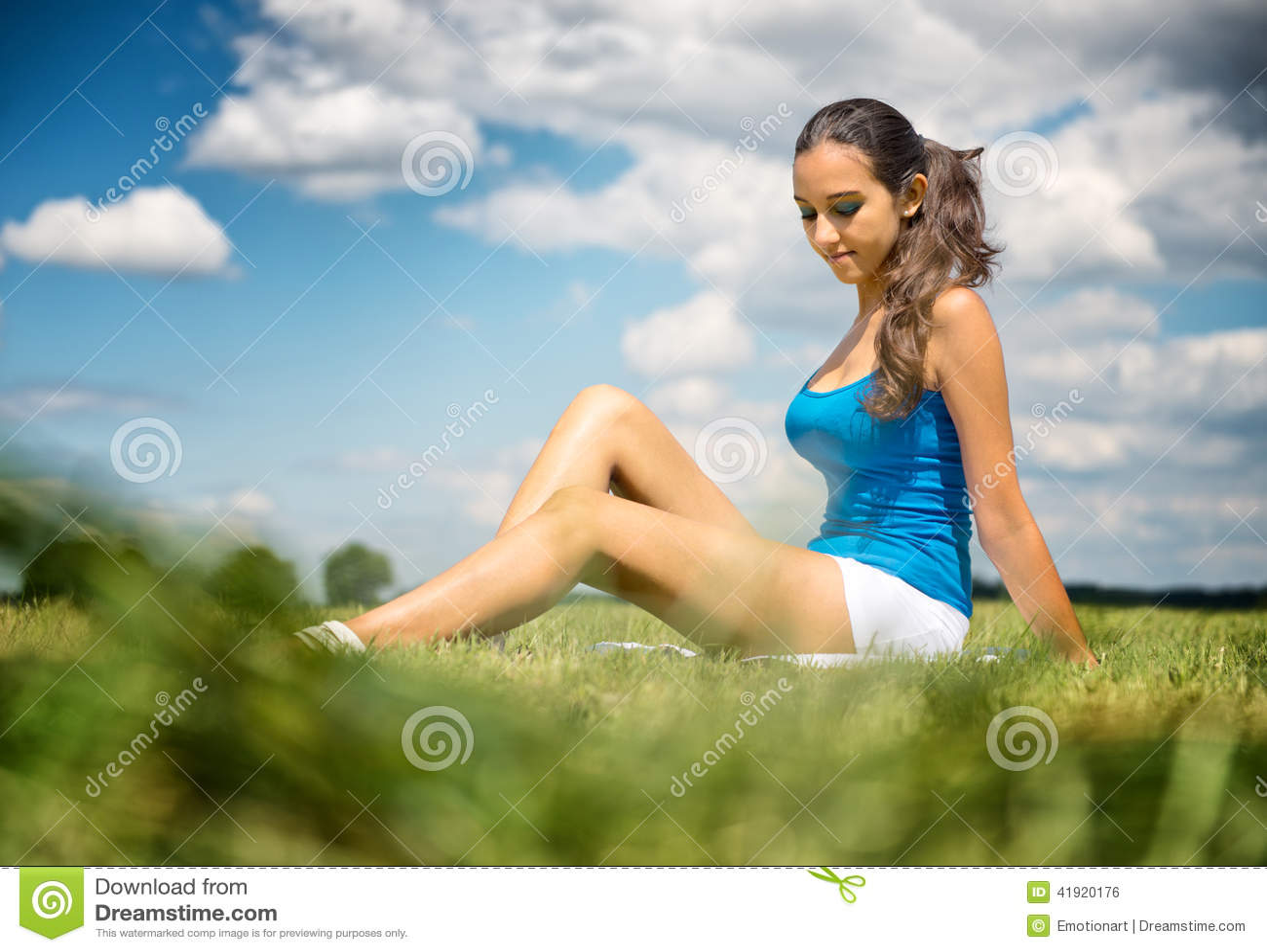 Muchacha hermosa que se relaja en un campo verde