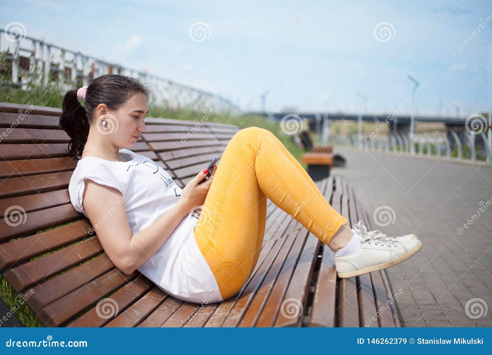 Muchacha hermosa que se sienta en banco en parque con el teléfono en manos