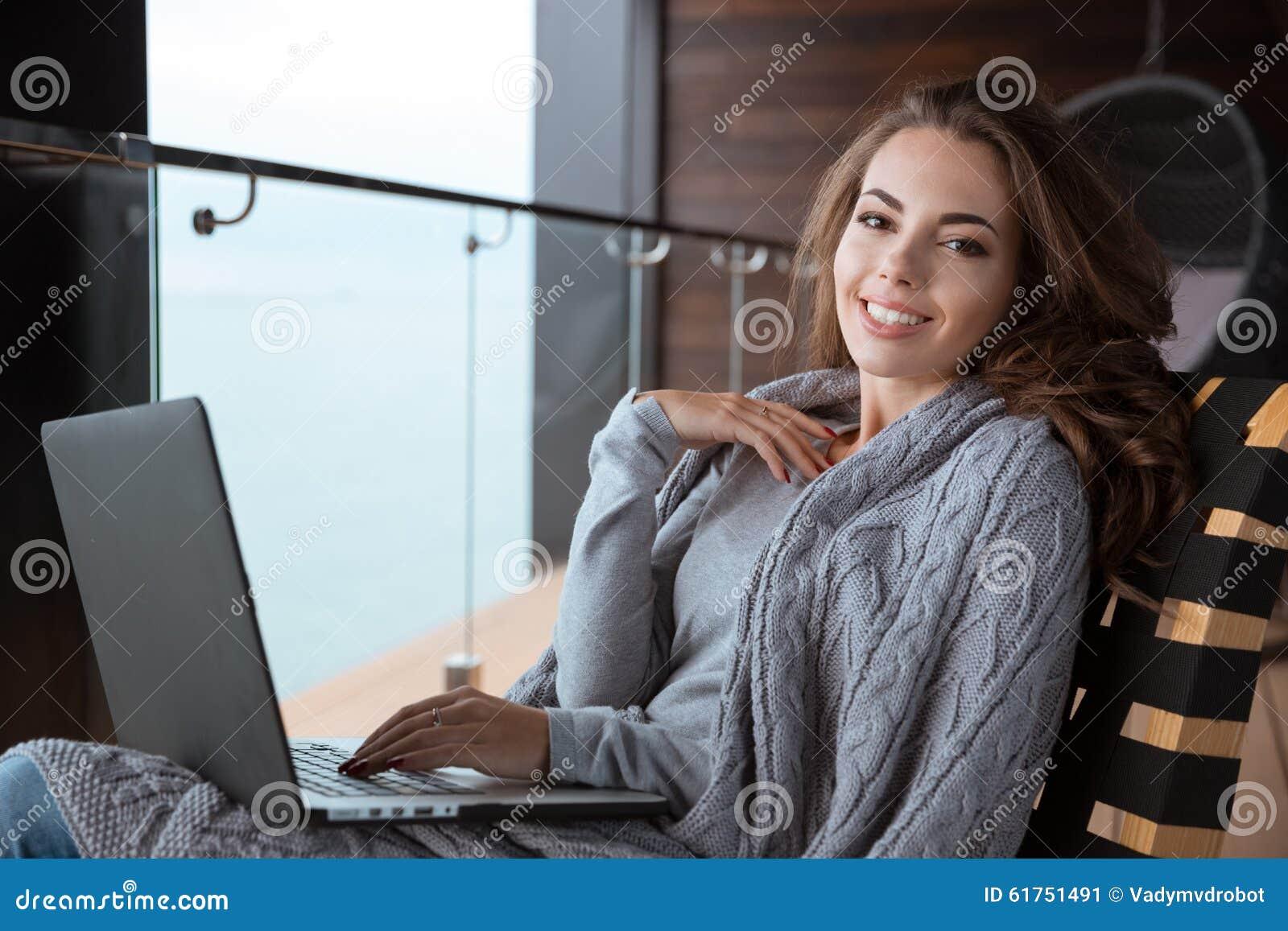 Muchacha hermosa que sonríe usando el ordenador portátil