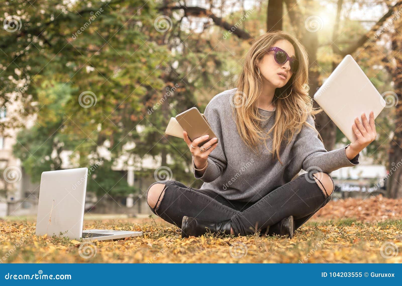 Muchacha histérica con demasiadas pantallas, mobils, tabletas y lapto
