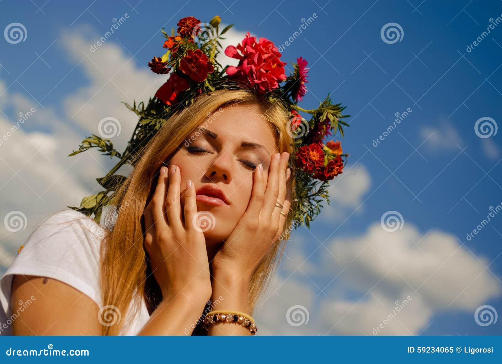 Muchacha imponente en guirnalda de la flor que sueña en azul