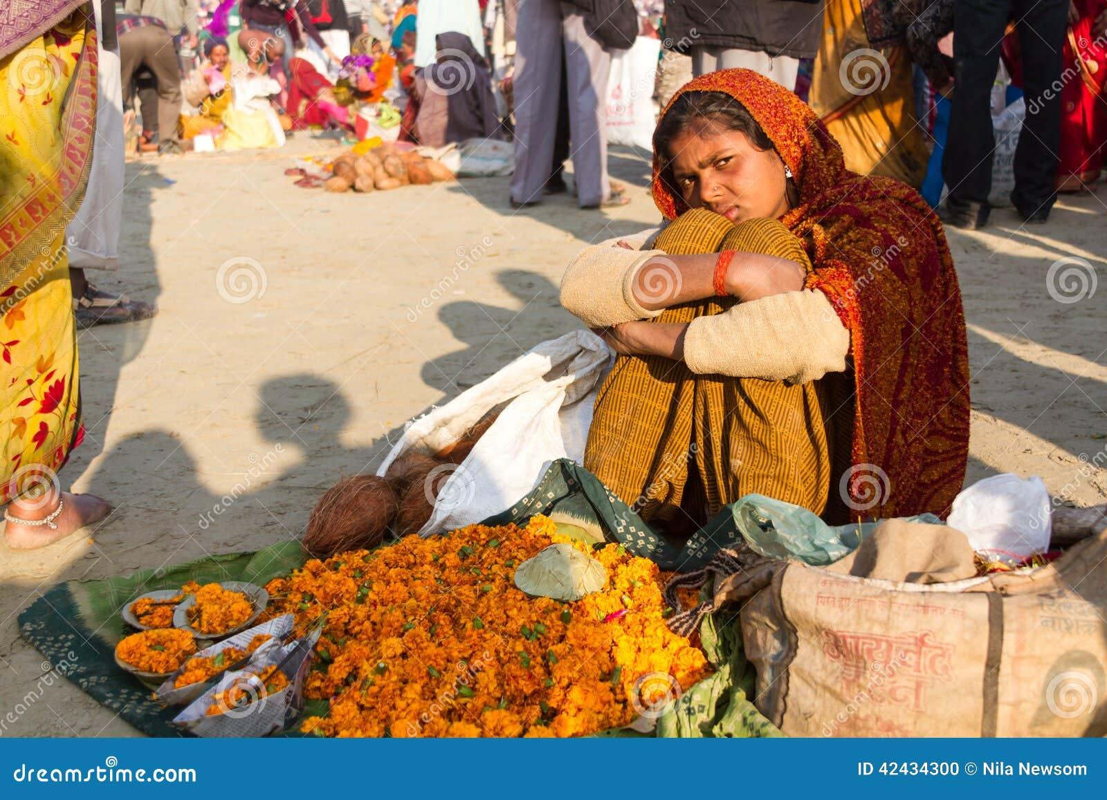 Muchacha india que vende las flores en el Kumbha Mela, la India