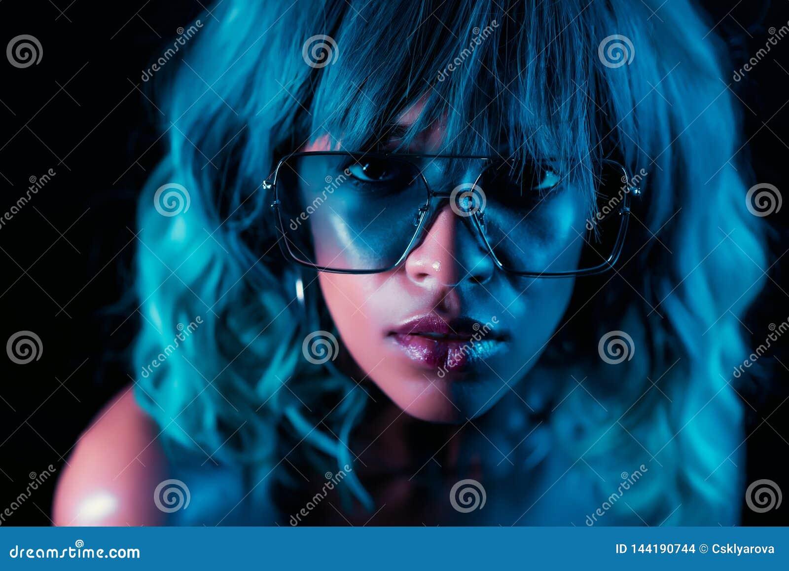 Muchacha inusual encantadora con el peinado y los vidrios azules Mujer atractiva con maquillaje perfecto y peluca que mira la cám