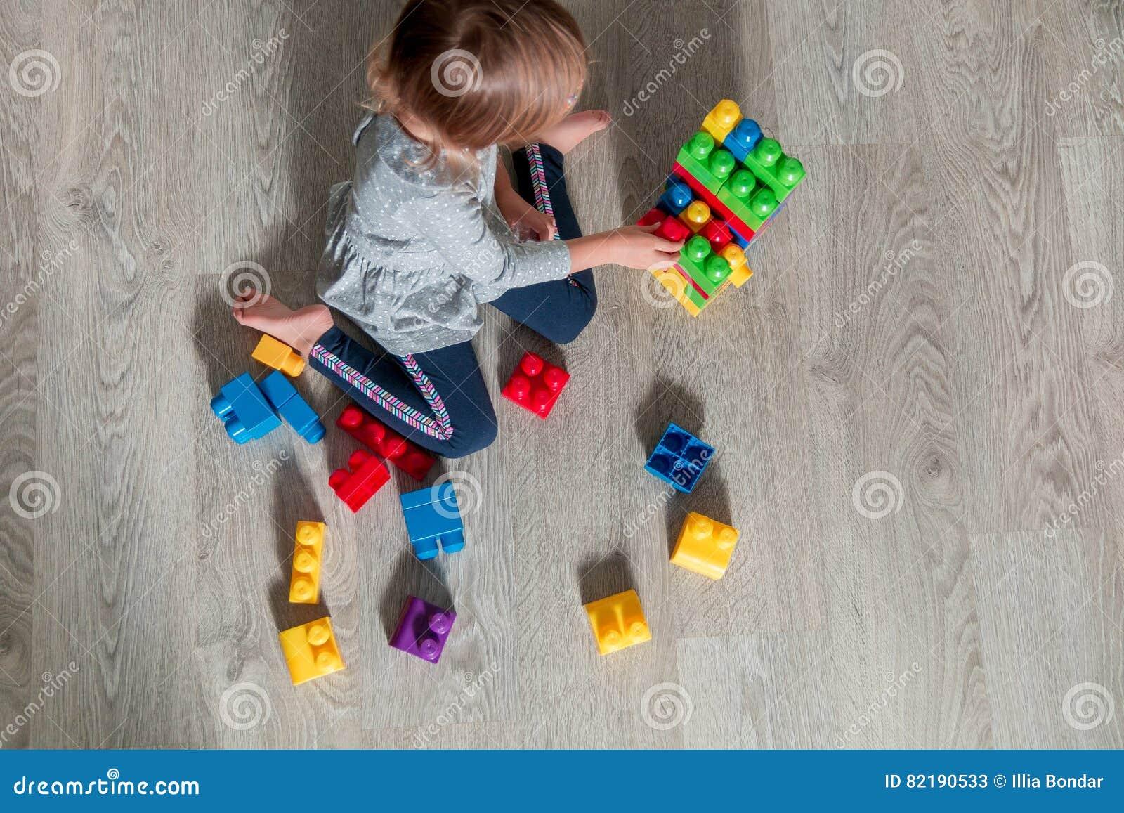 Muchacha irreconocible del niño que tiene la diversión y estructura de los bloques plásticos brillantes de la construcción Niño q
