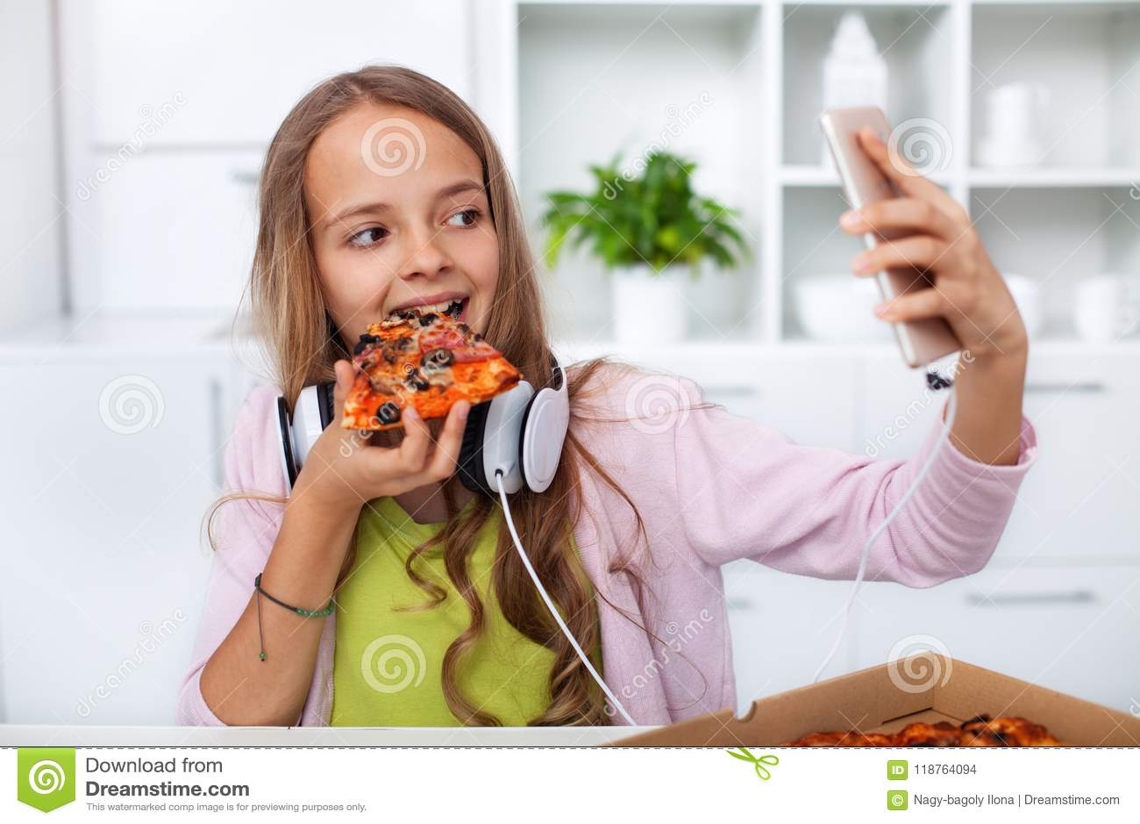 Muchacha joven del adolescente que come la pizza en la cocina - fabricación de un selfi