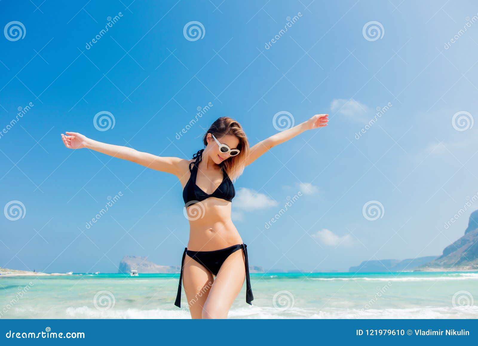 Muchacha joven del pelirrojo en bikini negro en la playa de Balos