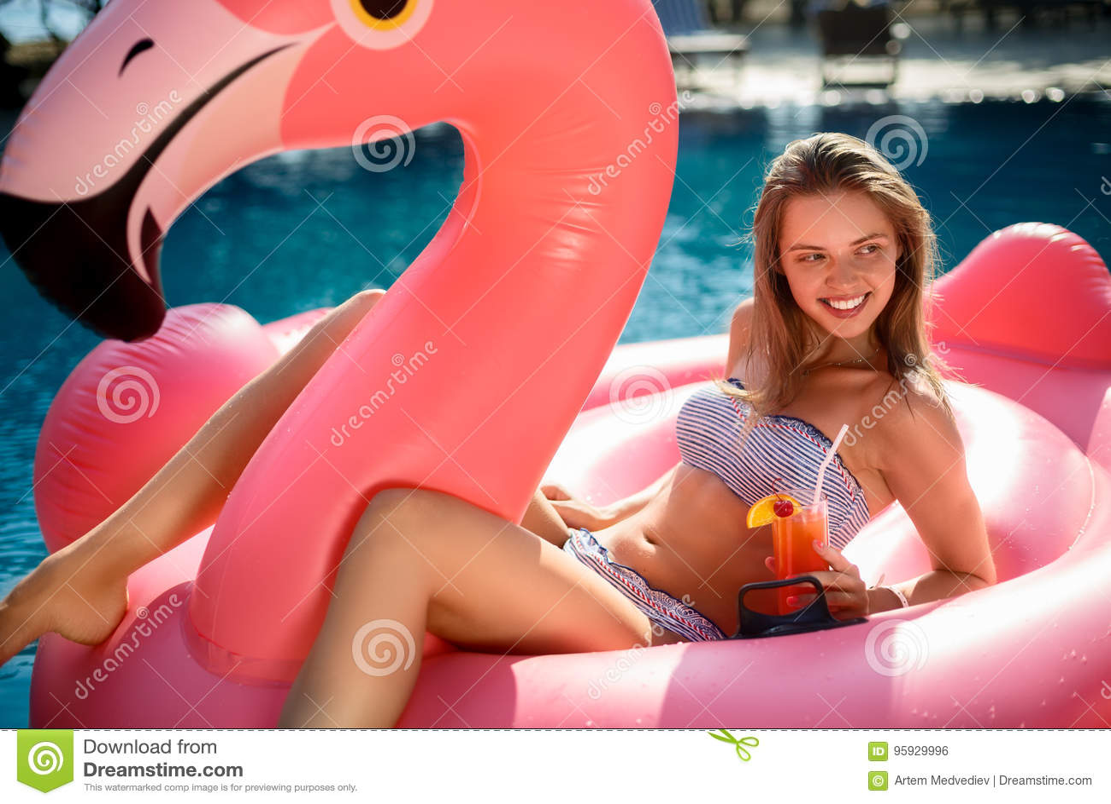 Muchacha joven y atractiva que se divierte y que ríe en un colchón rosado gigante inflable del flotador de la piscina del flamenc