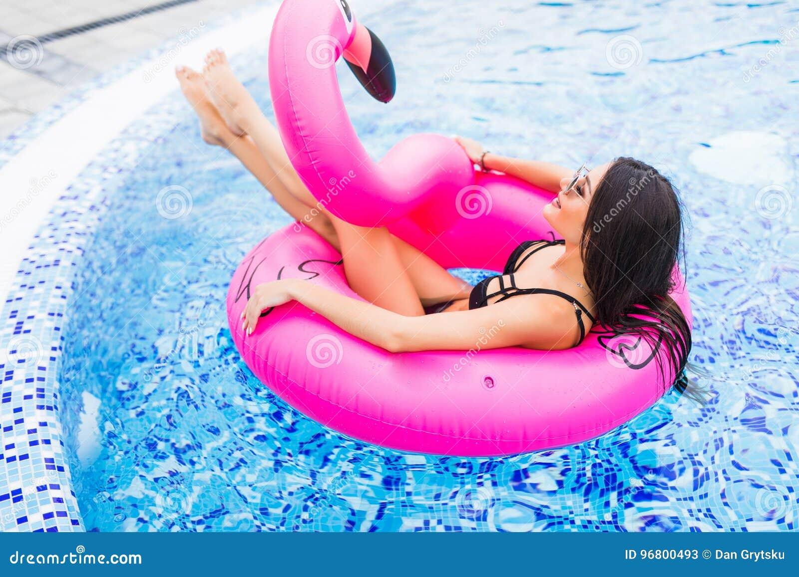Muchacha joven y atractiva que tiene mentiras en el sol un colchón rosado gigante inflable del flotador de la piscina del flamenc