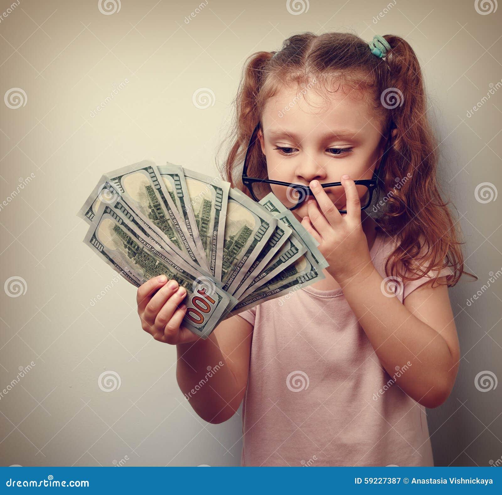 Muchacha linda del niño del negocio que sostiene el dinero y que cuenta los ingresos