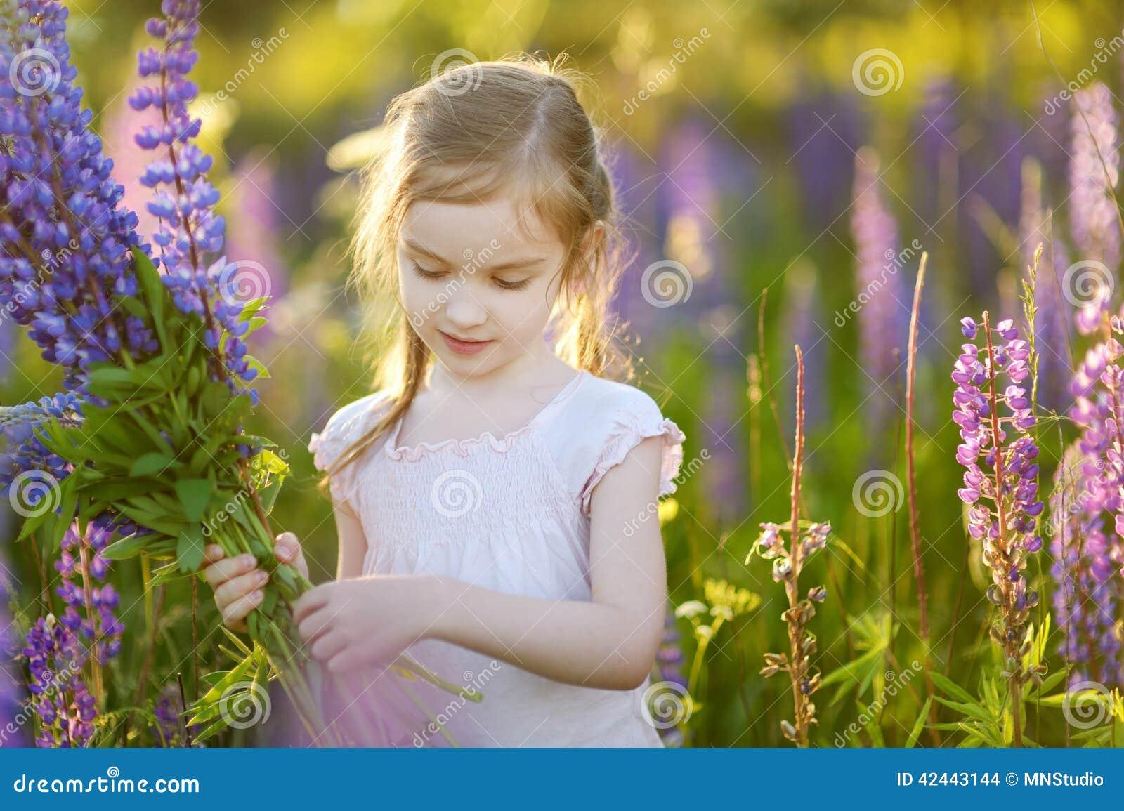 Muchacha linda en campo floreciente del lupine