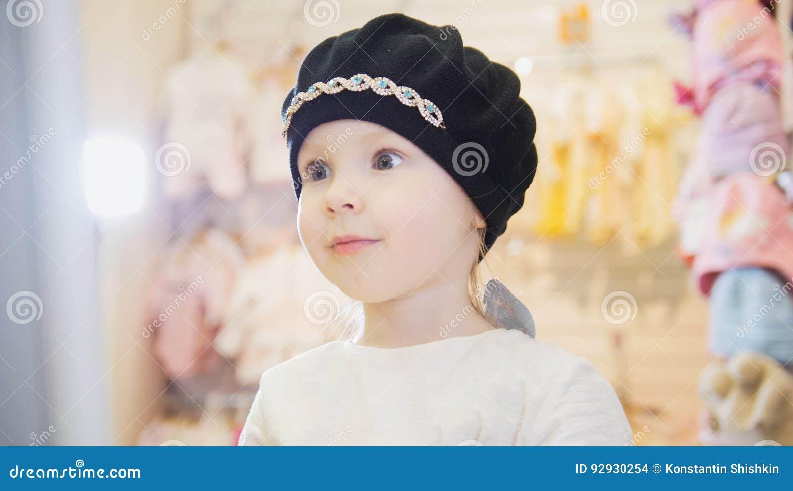 Muchacha linda en una boina negra delante de un espejo en una tienda de ropa  para los niños 6533998ec7f