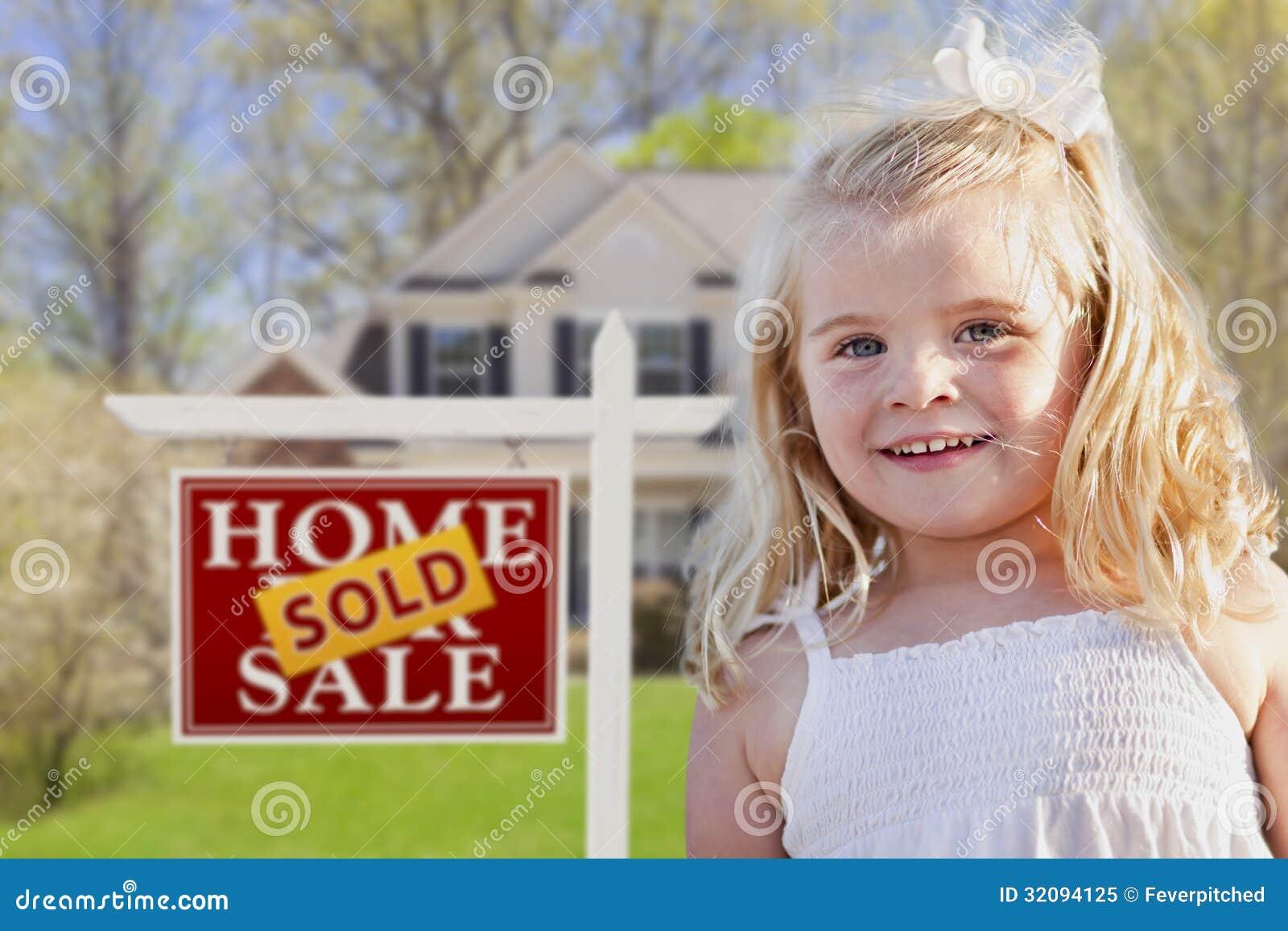Muchacha linda en yarda con vendido para la muestra y la casa de Real Estate de la venta