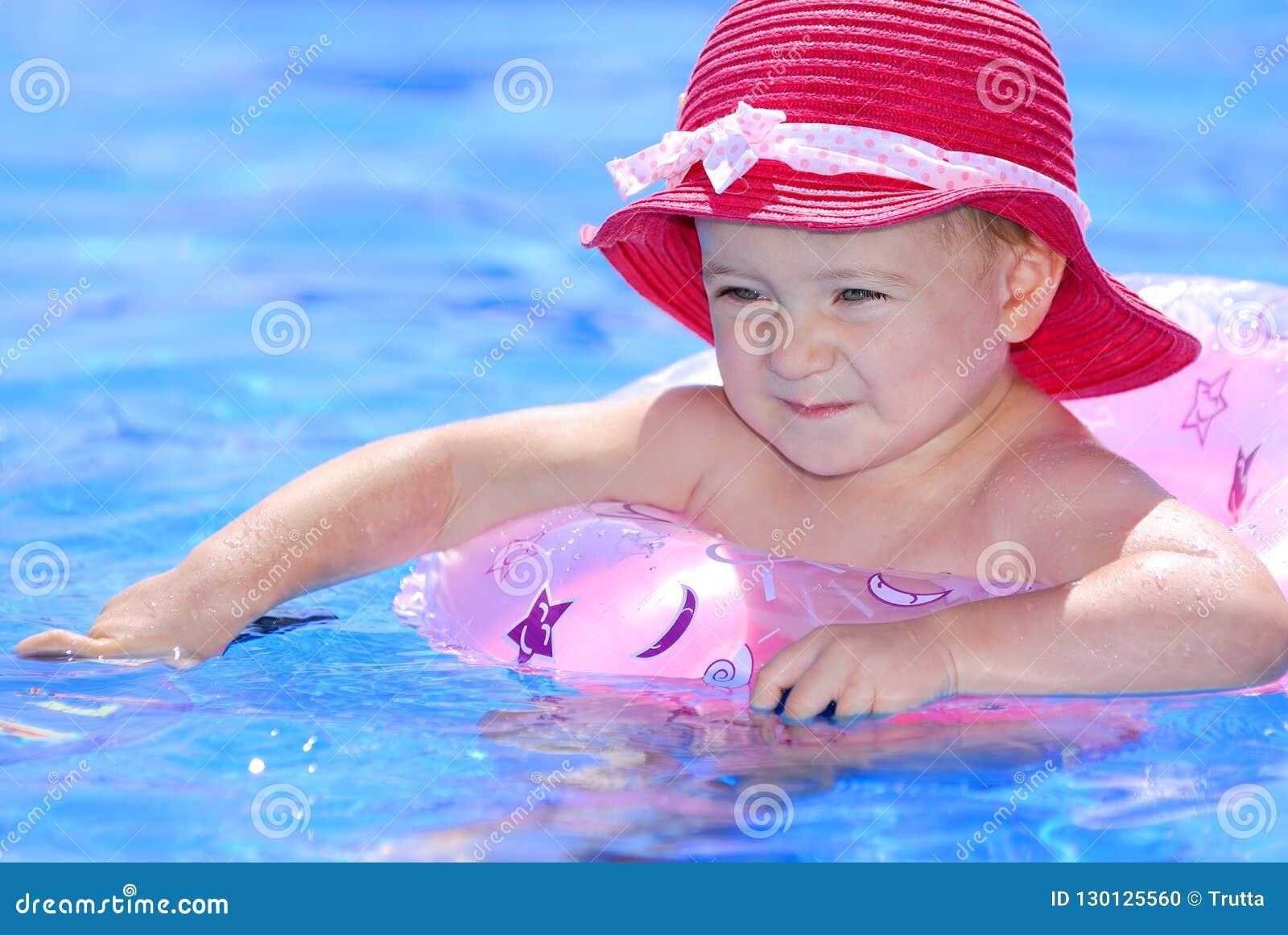 Muchacha linda que flota en un círculo inflable
