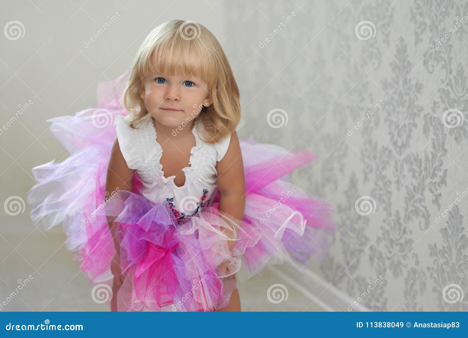 Muchacha linda que presenta en la falda rosada y violeta