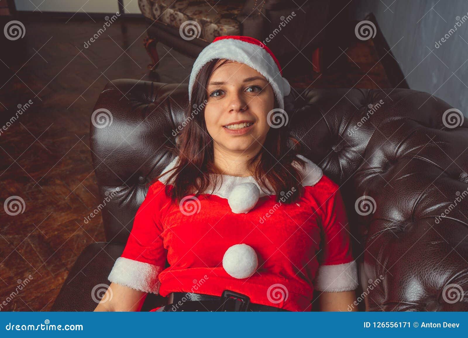 Muchacha linda vestida como Santa Claus ¡Feliz Año Nuevo y Feliz Navidad!