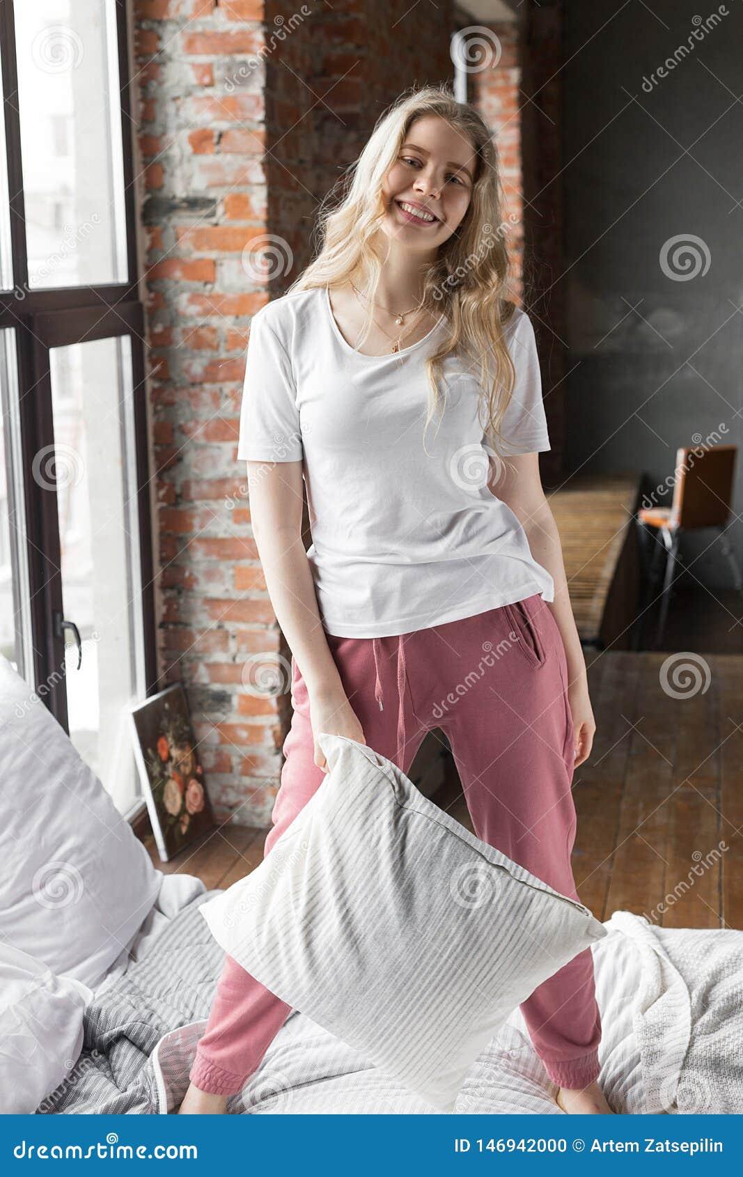 Muchacha linda vestida en el pijama que se coloca en una cama con una almohada y una sonrisa