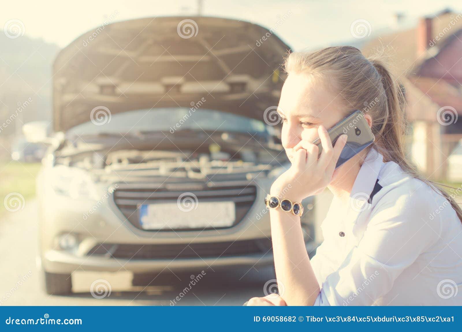 Muchacha llamada Coche quebrado en un fondo La mujer se sienta en una rueda Reparación atractiva de la mujer joven un coche Fondo