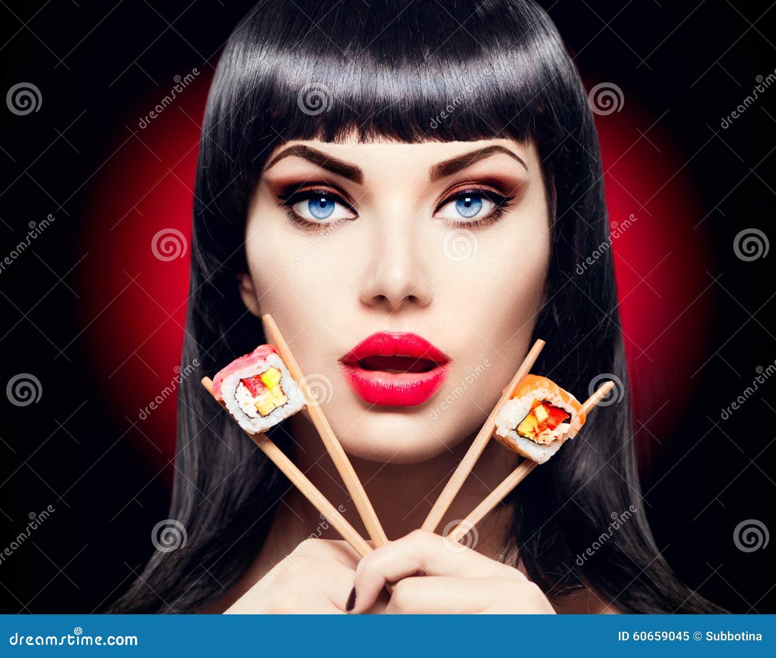 Muchacha modelo de la belleza que come los rollos de sushi