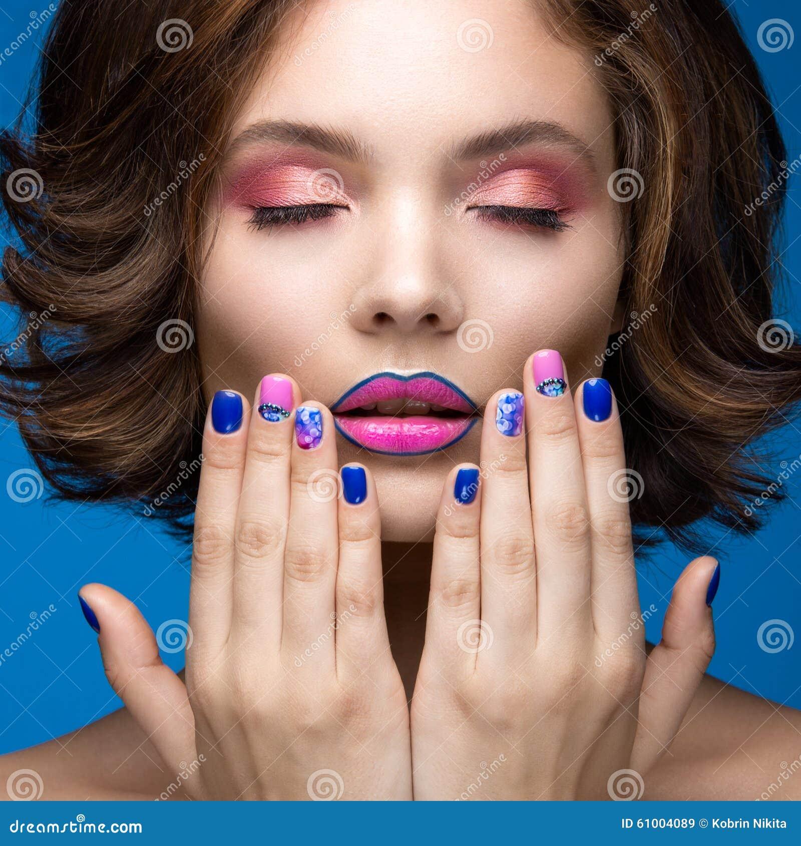 Muchacha modelo hermosa con maquillaje brillante y esmalte de uñas coloreado Cara de la belleza Clavos coloridos cortos
