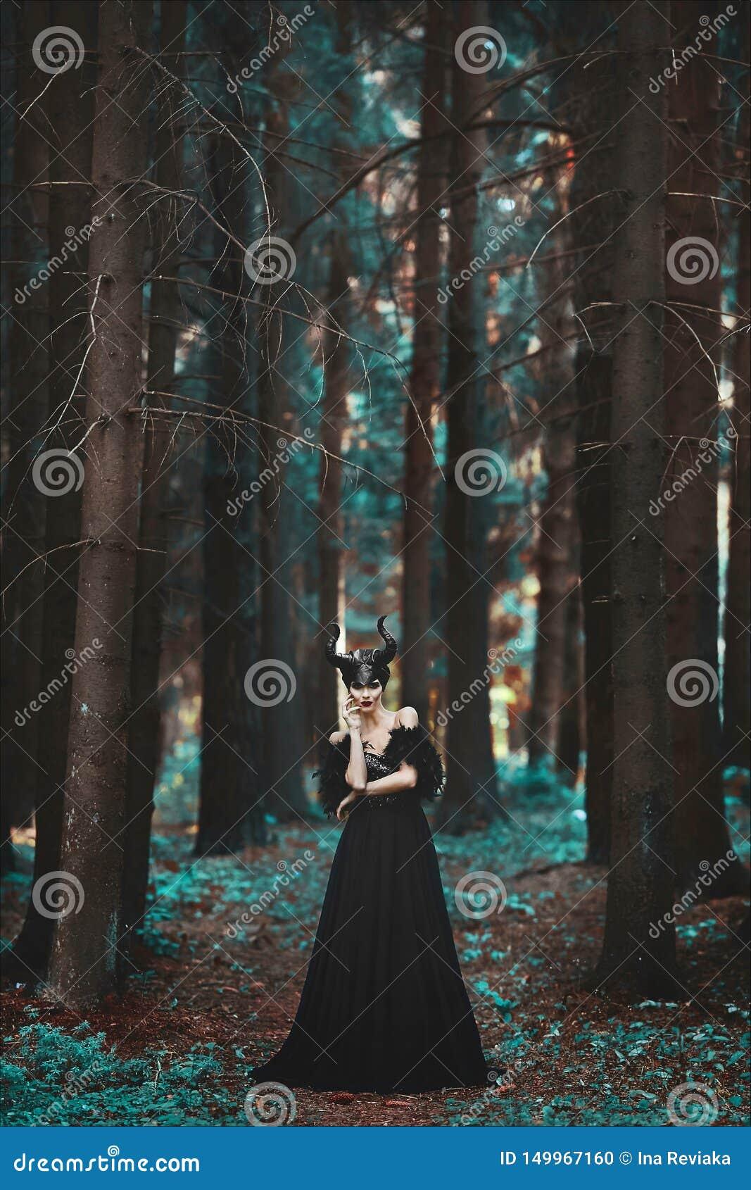 Muchacha modelo morena elegante y de moda en la imagen de la presentaci?n mal?fica entre bosque m?stico - historia del cuento de