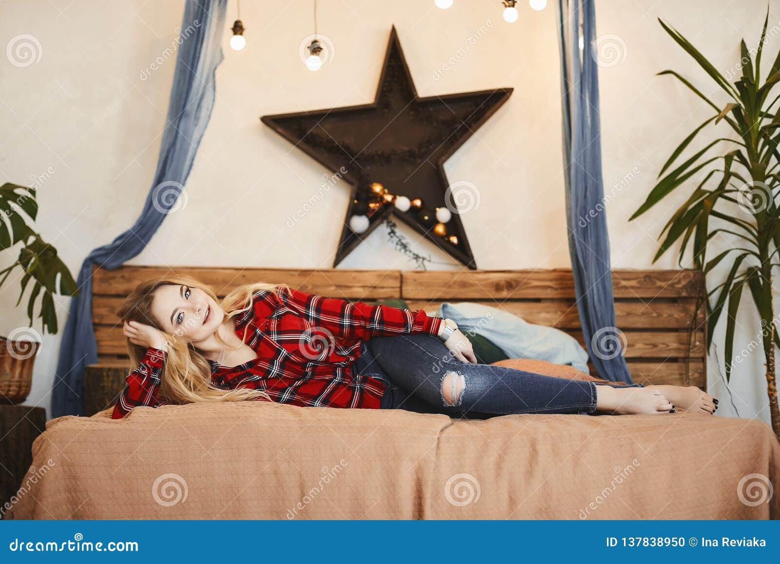 Muchacha modelo rubia feliz y de moda con una sonrisa encantadora en la camisa de tela escocesa roja y en restos de los vaqueros