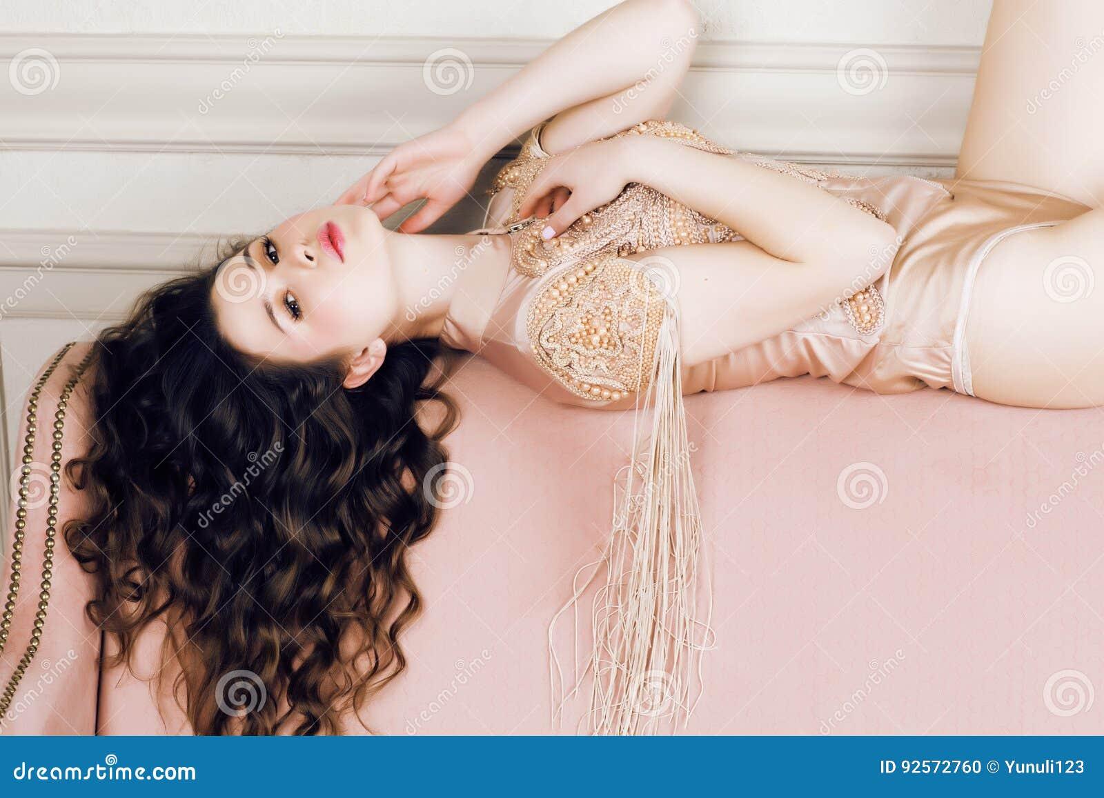 Muchacha morena bonita joven en vestido de la moda en el sofá que presenta en el interior casero rico de lujo, concepto moderno d