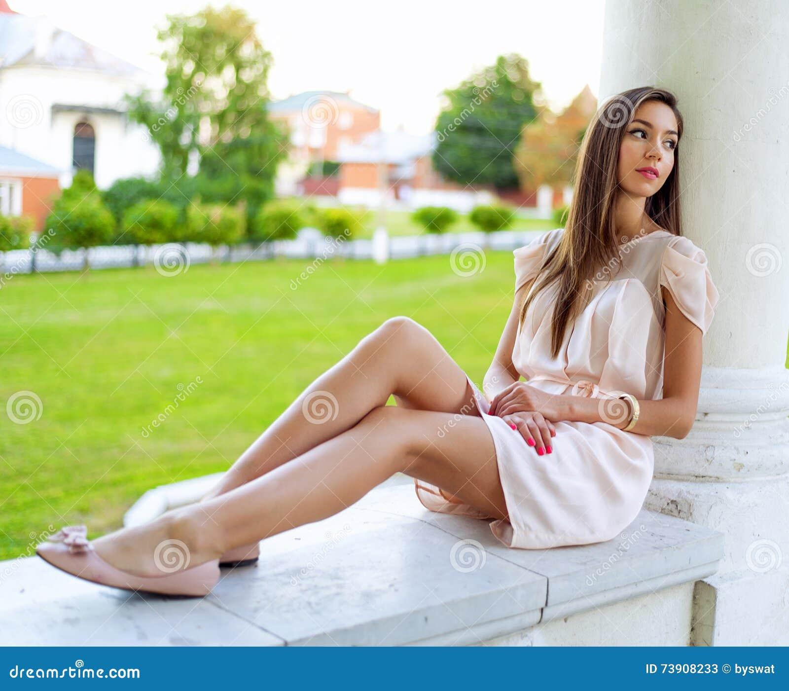 Muchacha morena hermosa que descansa en la sentada del aire abierto, soñando con la mirada en la distancia, mujer de negocios con