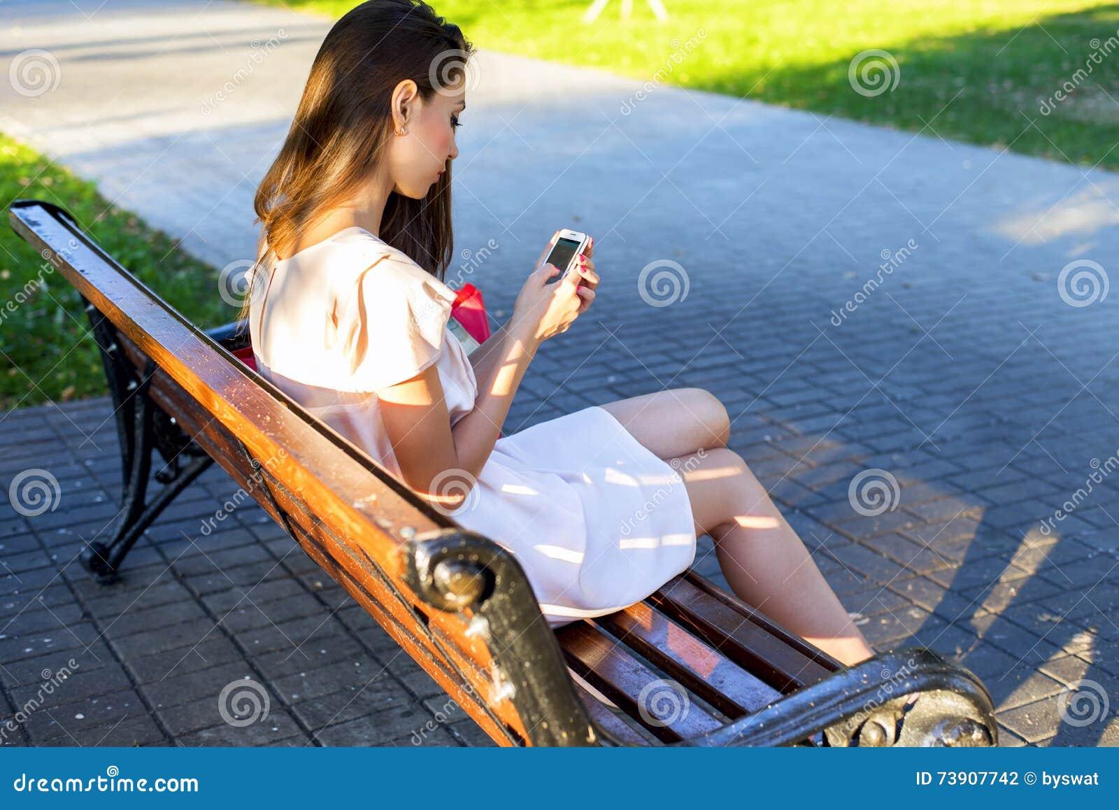 Muchacha morena hermosa que escribe un parque del teléfono del mensaje que se sienta en banco en el vestido, mujer de negocios de