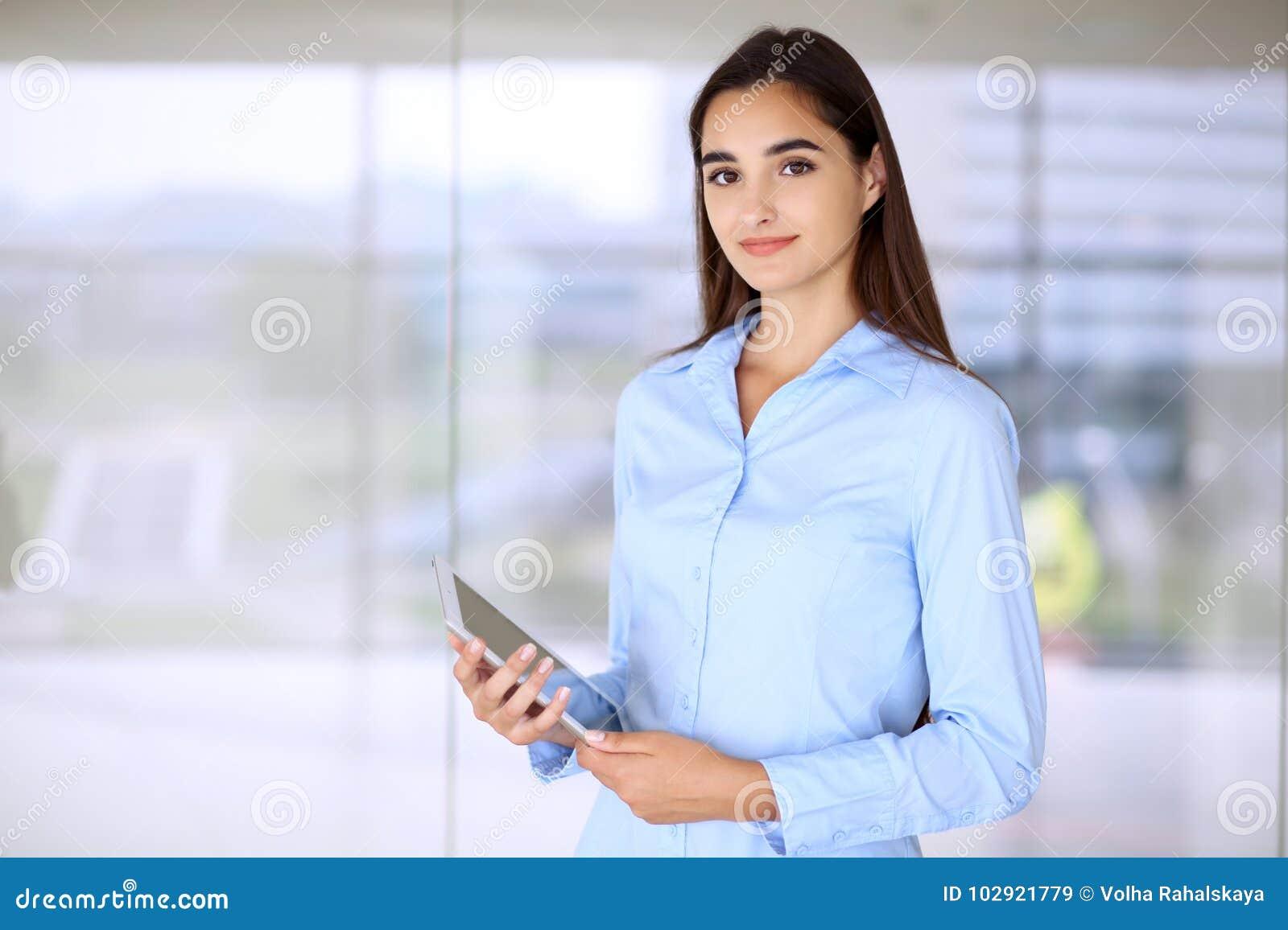 Muchacha morena joven de la empresaria o del estudiante que mira la cámara