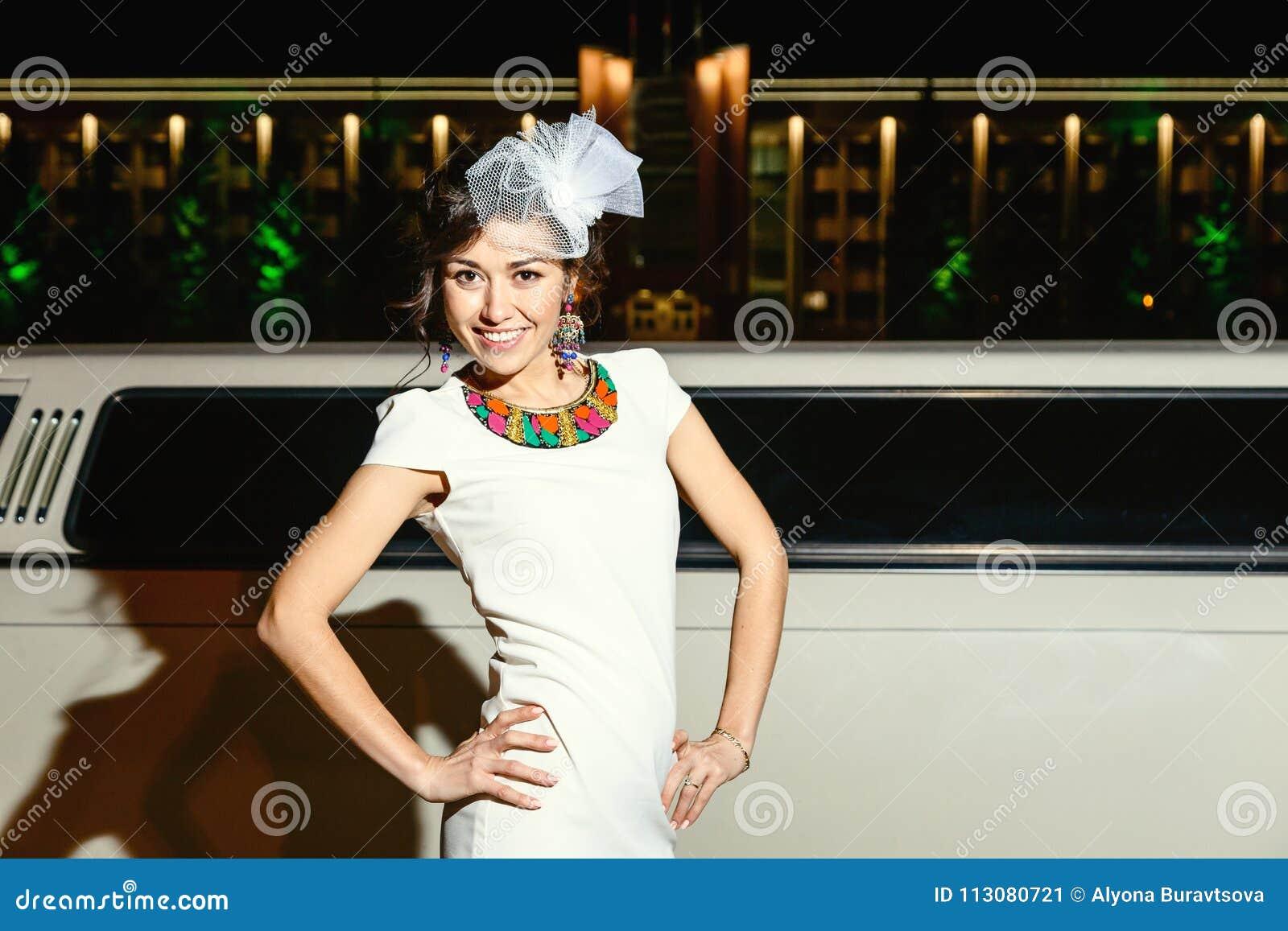Muchacha morena joven en el vestido y el sombrero blancos al lado de la limusina blanca