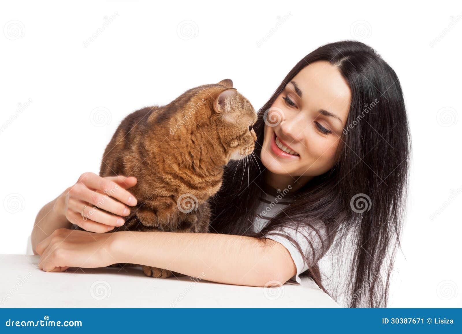 Muchacha morena sonriente hermosa y su gato del jengibre sobre los vagos blancos