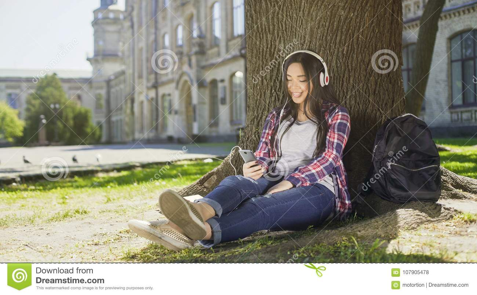 4a1edd15c Muchacha Multirracial Debajo Del árbol En Auriculares Con El ...