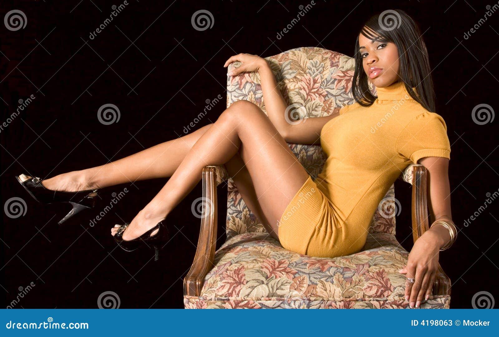 Muchacha negra atractiva en silla