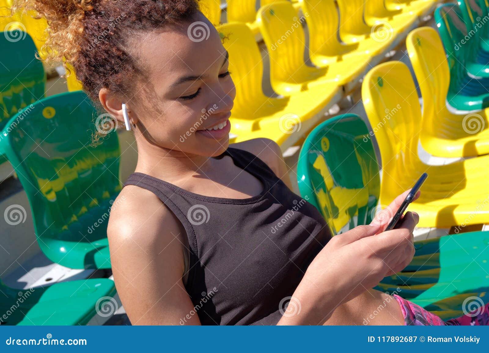 Muchacha negra juguetona atractiva joven que se sienta solamente en una butaca para los espectadores en el estadio Airpods blanco