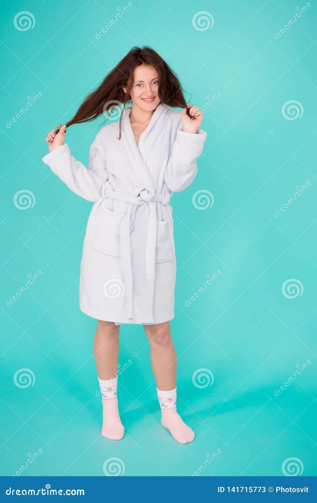 Muchacha ningún maquillaje hacer frente al fondo largo de la turquesa de la albornoz del desgaste del pelo Aliste para los proced