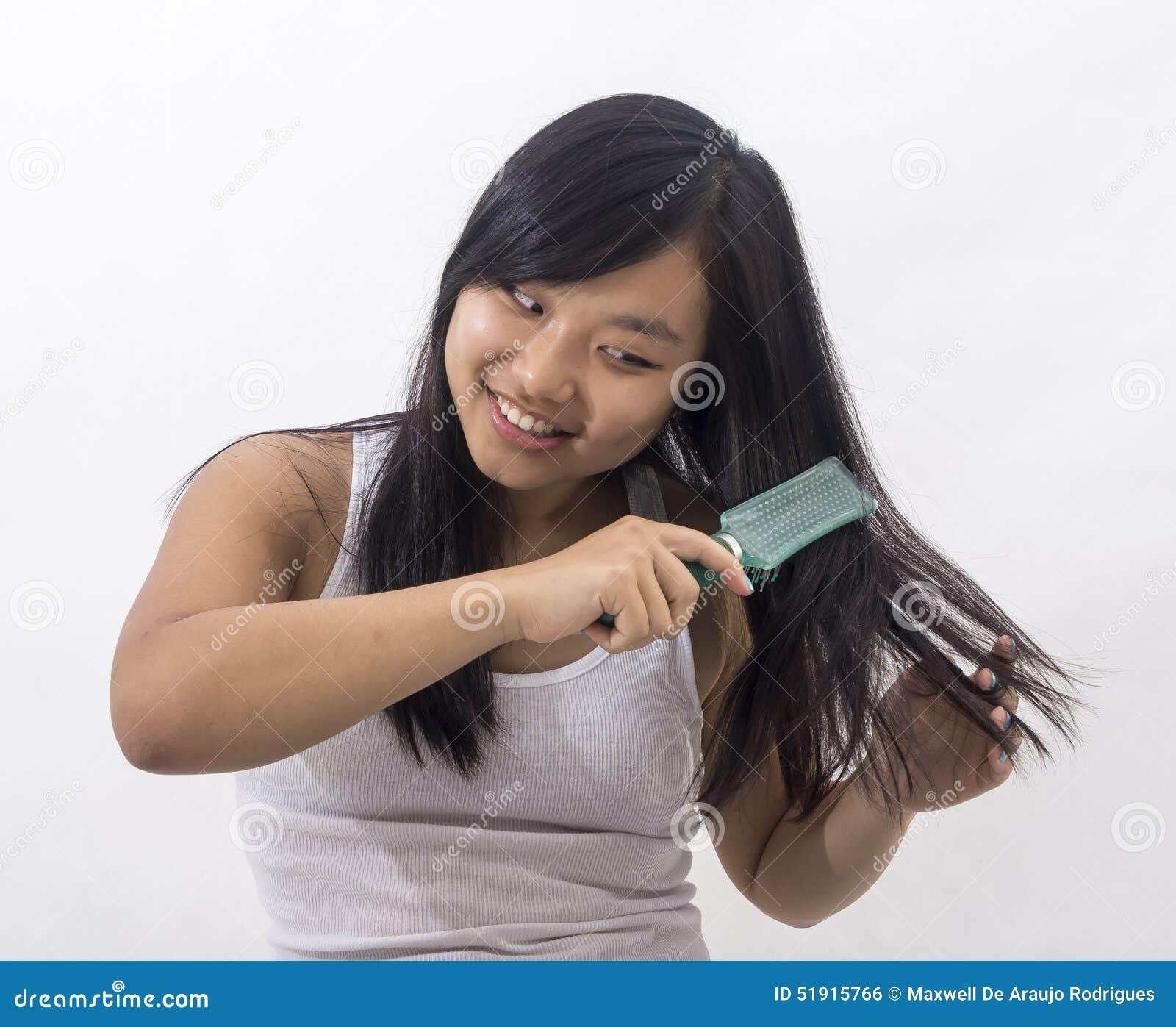 Muchacha oriental sonriente que cepilla su pelo
