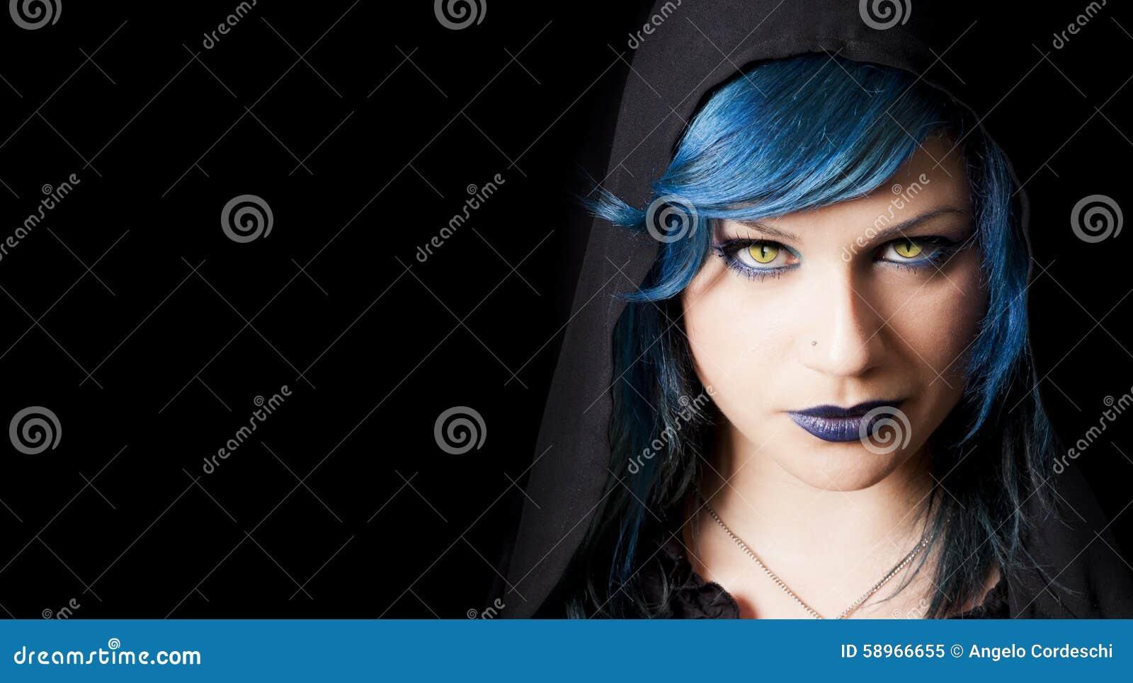 Muchacha oscura con los ojos de gatos amarillos, el pelo azul y la capilla negra