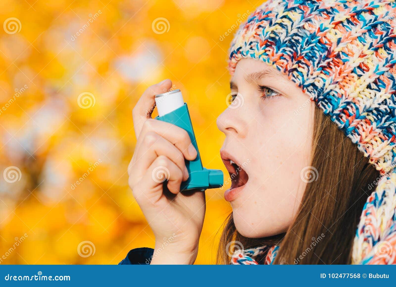 Muchacha paciente del asma que inhala la medicación para tratar la brevedad o