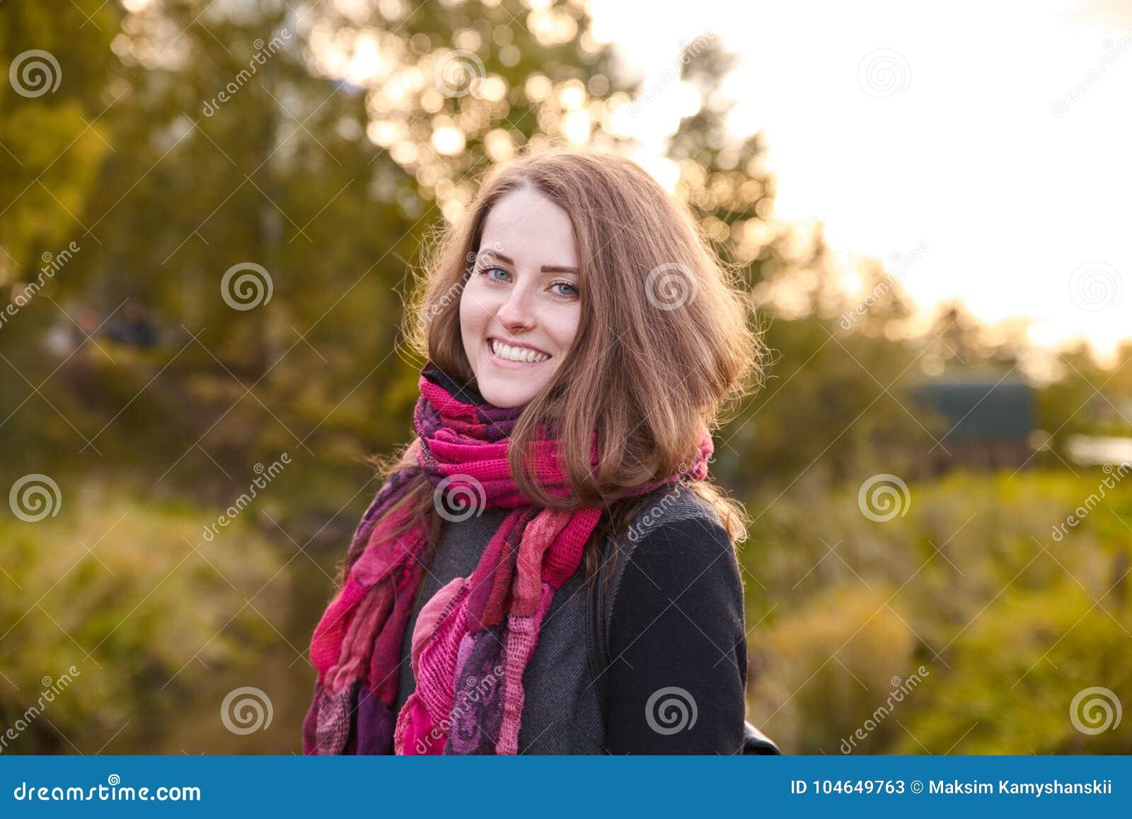 Muchacha pelirroja atractiva joven que presenta para un retrato en los vagos