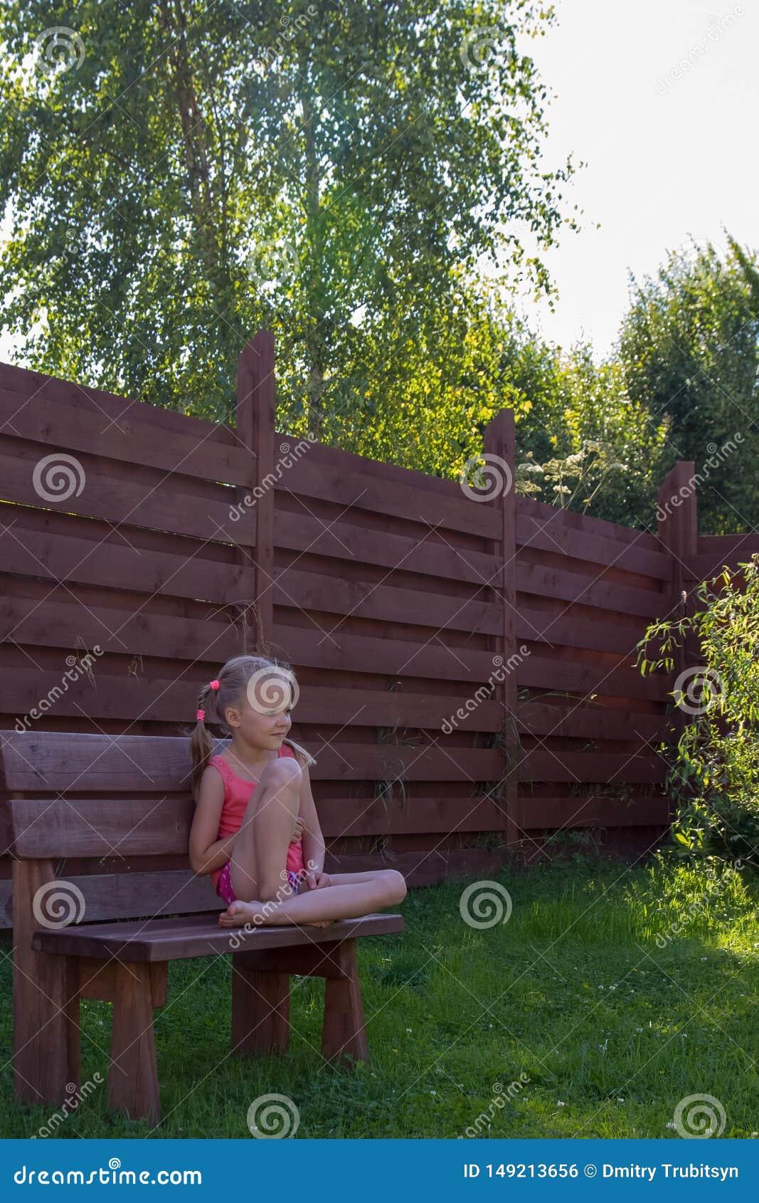 Muchacha pensativa que se sienta en banco de madera