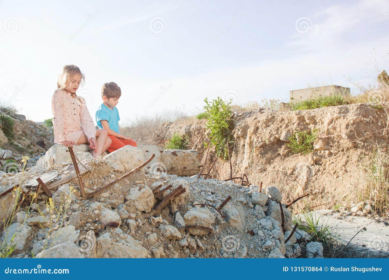 Muchacha pobre del muchacho de dos niños del refugiado en la construcción de las ruinas destruida por ataque aéreo