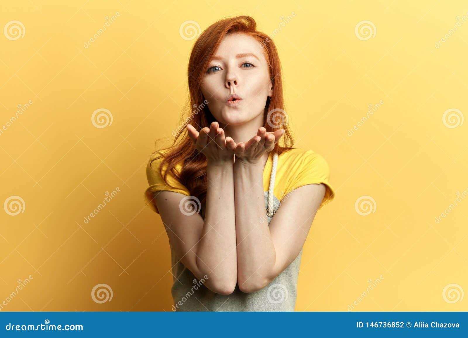 Muchacha preciosa del jengibre en el equipo casual que envía beso que sopla