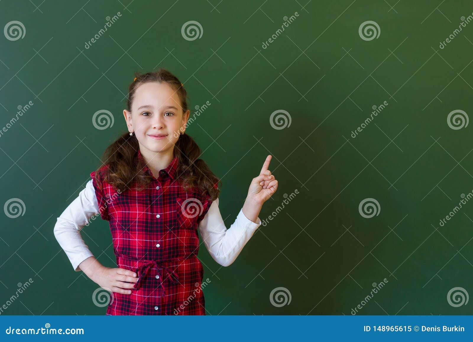 Muchacha preescolar de la colegiala feliz en la situaci?n del vestido de la tela escocesa en clase cerca de una pizarra verde Con