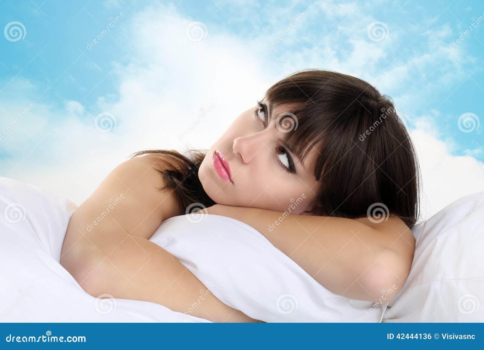 Muchacha principal en la almohada con el cielo azul en fondo