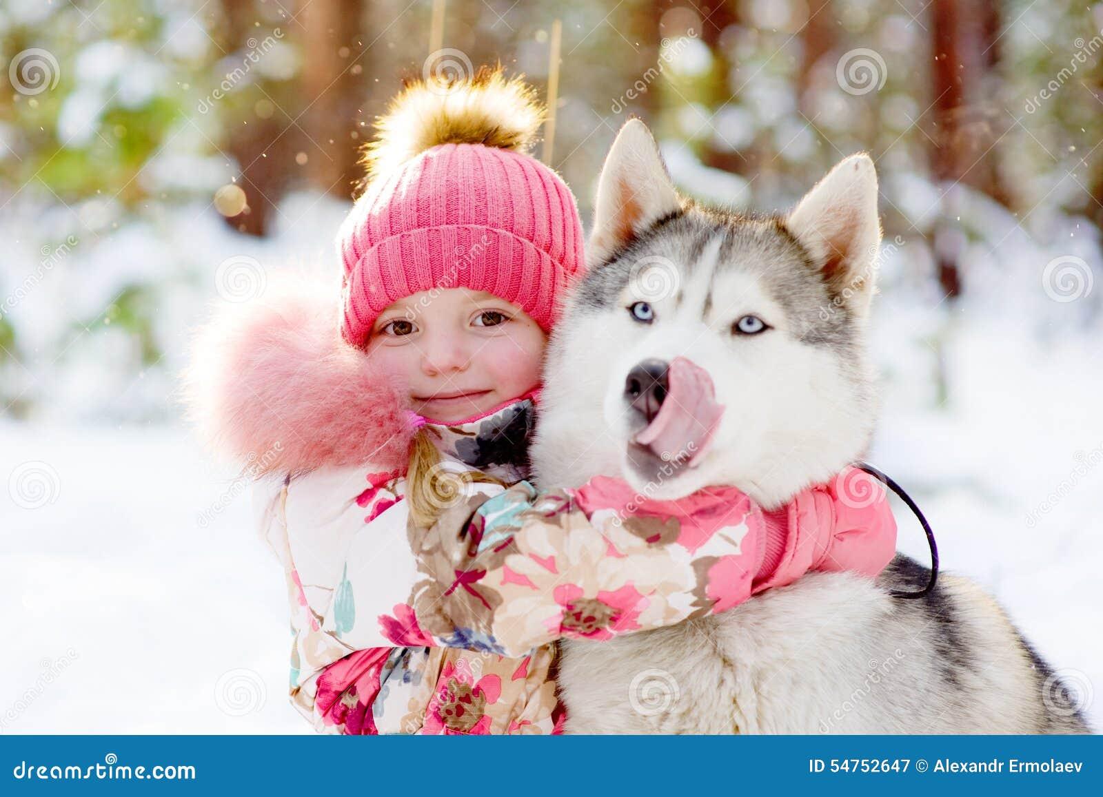 Muchacha que abraza perros esquimales en bosque del invierno
