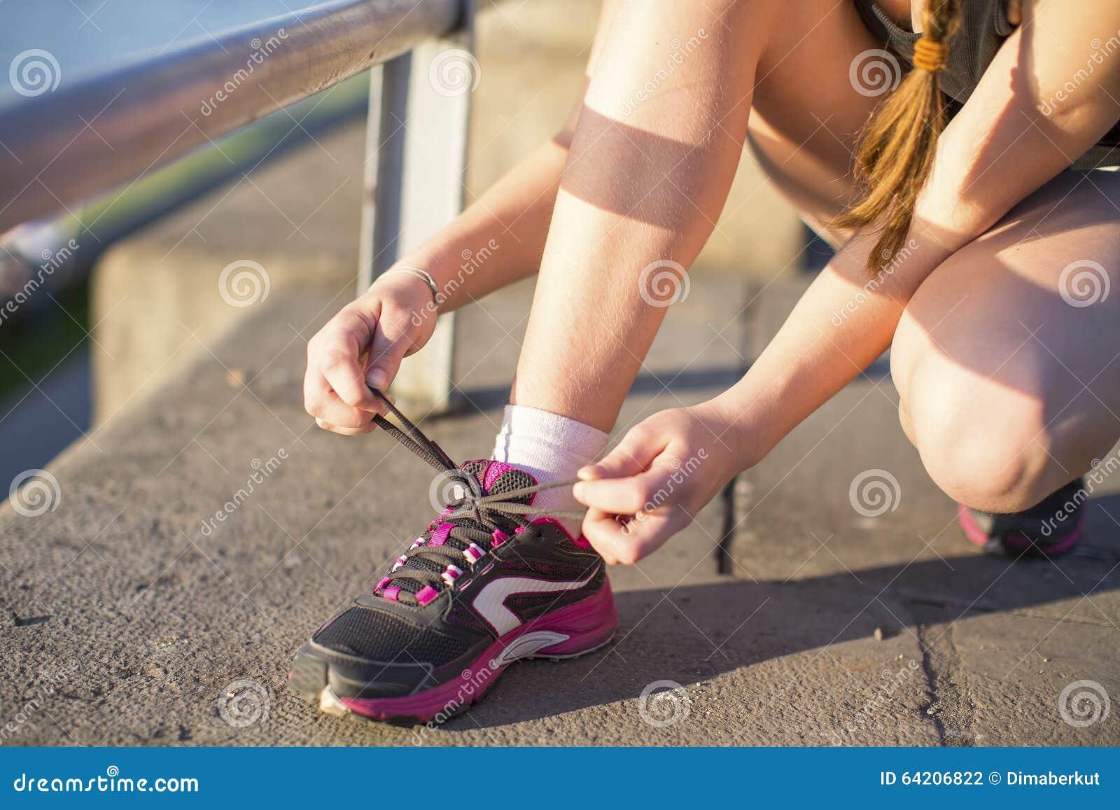 Muchacha que ata cordones en las zapatillas de deporte