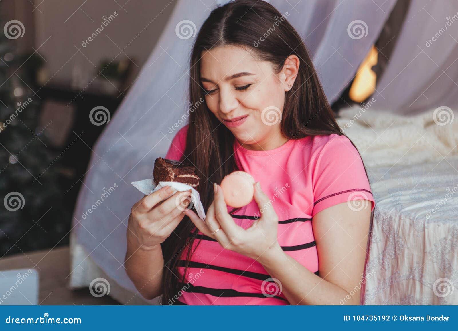 Muchacha que come la torta browny sabrosa con en el dormitorio Postre dulce Buenos días